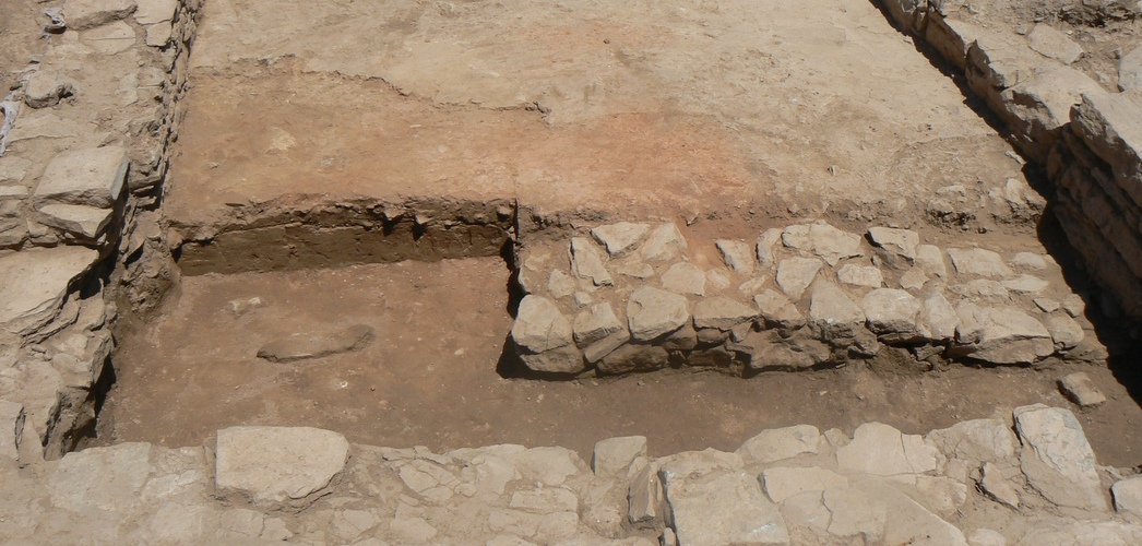 The process of excavating the hearth (redder area). At the bottom of the picture can be seen the test trench thanks to which the wall from the intermediate phase was discovered